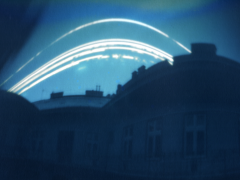 A felvételen szépen látni -igen komoly torzítással- a harmadik emelet teljes panorámáját, a tűzfalat, a havas tetőt,a Nap hiányos égi útját...a márciusi 15-i rendkívüli havas időszak nyomait. A fotó feldolgozását, a GIMP 2.6 programmal végeztem el. A felvétel, 2013 március 6 és április 2-a közti időszakot fedi le Film: Bromofort ISO 200 BN0 Budapest irány: Dél  A lyukkamera egy 35mm-es filmes dobozból lett kialakítva. Földvári István Zoltán felvétele