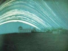 Hannák Judit felvétele a Sülysápi Csillagvizsgálóról. A felvételen nagyon szép részletességgel látszik a csillagvizsgáló épülete és a környező növényzet is. Még kissé az eredeti színeket is visszaadja a kép. A kamera egyenesen a csillagvizsgáló irányában lett kihelyezve. Kár hogy a tetején már nem látszik a Nap útja, de így is nagyon szép és érdekes a felvétel. Készült: 2013. augusztus-tól 2013 december 20-ig. Mindkét kamera Ilford papírra készült, melyet Kálmán Attilától kaptam kipróbálásra. Dél, dél-kelet felé néztek a kamerák.