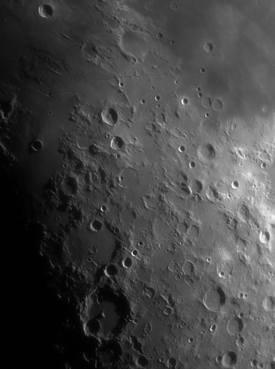 Manilius, Hyginus, Triesnecker, Rhaeticus, Hipparchus, Albategnius, Parrot kráterek (és még sokan mások) a terminátor közelében. A központi felfödi régió északi pereme. Karácsonyi séta a Holdon – 2017-12-25 18:01:34 CET (17:01:34 UT) – Göd – 5000 frame-ből a legjobb 300. Távcső: 150/1200 Skywatcher Fraunhofer refraktor (akromatikus lencsés távcső). Mechanika: SkyWatcher HEQ-5 Pro mechanika SynScan vezérléssel, Kamera: ASI 174MM monokróm kamera. Szűrő: Baader vörös színszűrő (Baader Color-Filter Red 610nm Longpass 1 1/4″). Fókusznyújtás: Tele Vue POWERMATE 2.5x – 1.25″. Tóth Krisztián felvételén a holdi észak (nagyjából) felül van.