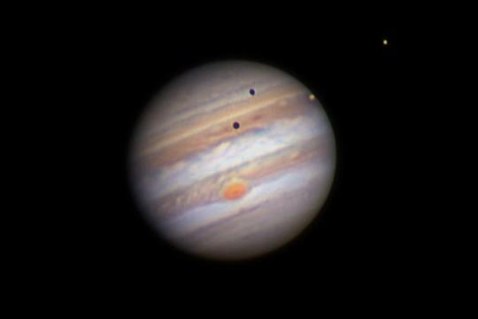 A Jupiter Szántó Szabolcs felvételén, 2017. május 29-én 19:51 UT-kor. A déli egyenlítői sávban (SEB) a Nagy Vörös Folt a centrálmeridián felé közelít. A NEB projekcióiból sötét füzérek futnak az egyenlítői zónába. A korong peremén az Io, a korongon kívül az Europa látható, mindkét hold árnyéka a bolygókorongra vetül. Észak lefelé van; 25,4 T.